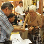 Mayor Fortunato R. Abrenilla handing out cash  assistance to a recipient from Bunga Mar.